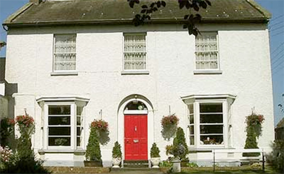 traditional white house with red door and bay windows either side door/