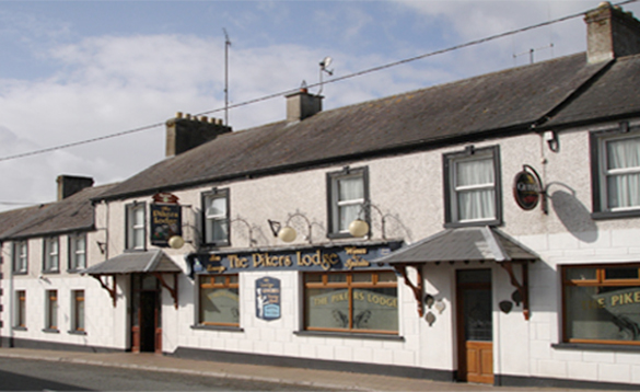 street view of a traditional two storey white painted Irish pub/