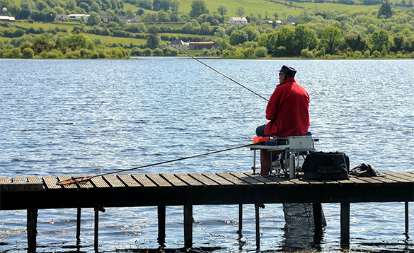 Angler fishing from a wooden jetty on a lake in Ireland/
