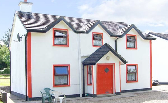 Large white detached self-catering house with red door at Riverbank Cottages, Scarriff/
