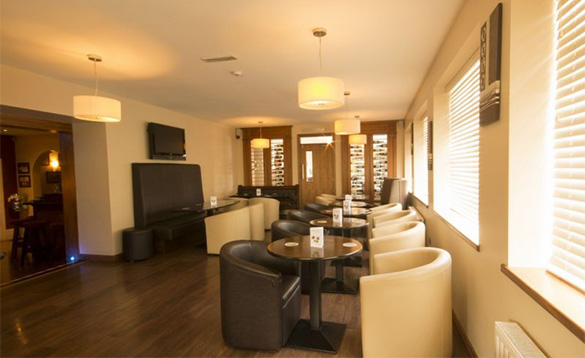 hotel lounge with dark wood tables and cream and brown leather chairs/