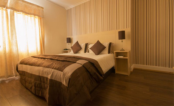 hotel bedroom with double bed with brown and cream linen, oak wood floor and brown and cream striped wallpaper/