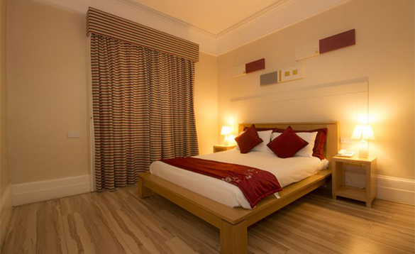 hotel bedroom with double pine bed with white and red bed linen and pine laminate flooring/