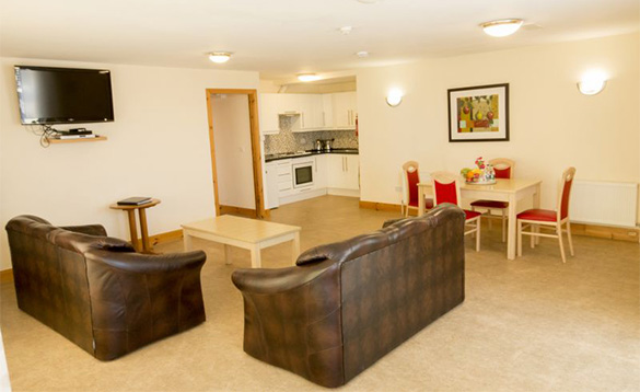 kitchen, lounge, dining area with two brown leather settees and cream table with cream and red chairs/