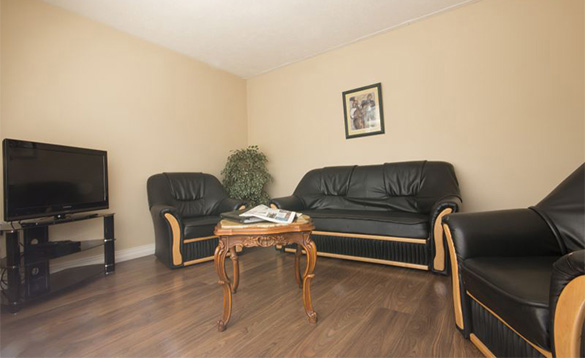 lounge with black leather three piece suite arranged around a television/