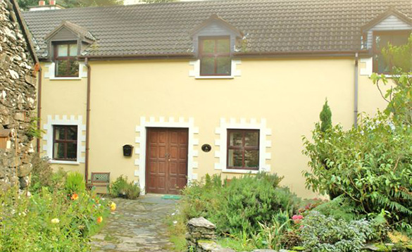 stone pathway leading through mature gardens to yellow painted two storey house/