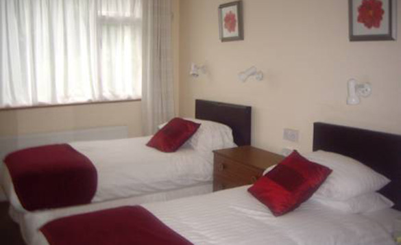 cream painted bedroom with two single beds with white bedding, red throws and cushions/