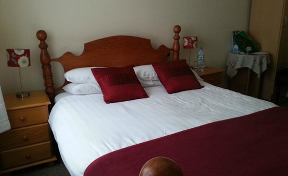 bedroom with pine double bed with white bedding and red throws/