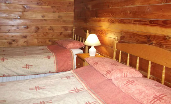 bedroom with pine clad walls and a double and single bed with pink patterned bed linen/
