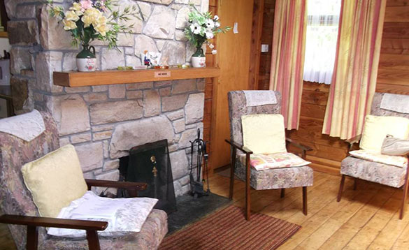 three high seat chairs arranged around a feature stone fireplace with open fire/