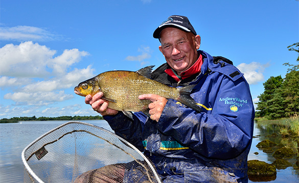 Angler sat at the edge of Lough Derg in Portumna, Ireland holding a recently caught bream/