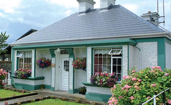 Entrance to Oak Park Lodge, a B&B accommodation in Portumna - white bungalow with green painted highlights and flower filled hanging baskets/
