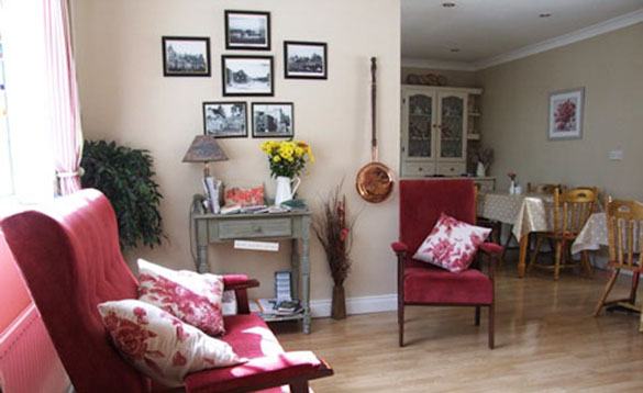 Living/dining room at Oak Park Lodge Guest House, Portumna with table set for breakfast/