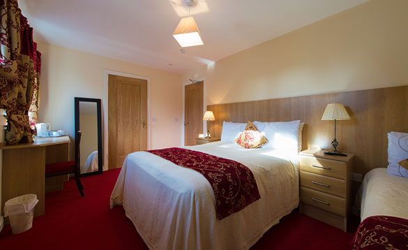 bedroom with double and single bed, red carpet and full length mirror in the corner/