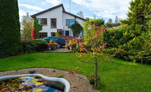 garden with samll pond, lawn and bushes and a two storey white house in the background/