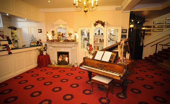 hotel reception with patterned red carpet, white open fireplace with fire alight and a grand piano in the centre of the room/