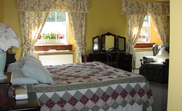 double bed room with yellow walls and a patchwork bedspread/