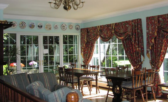 large conservatory with two dining tables and chairs and blue striped three piece suite/