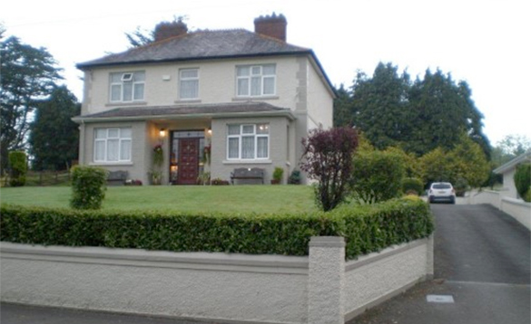 two storey house with trees behind and lan and hedge to the front/