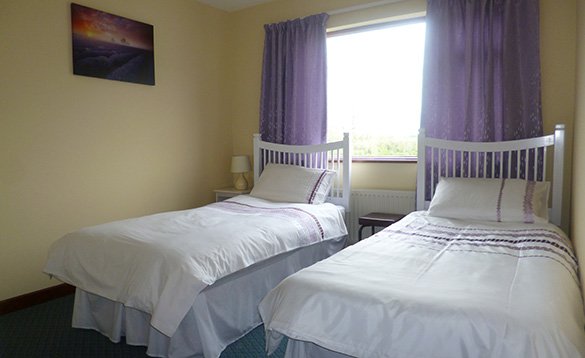 yellow painted bedroom with twin beds with white linen with lilac stripes infront of a window with lilac curtains/