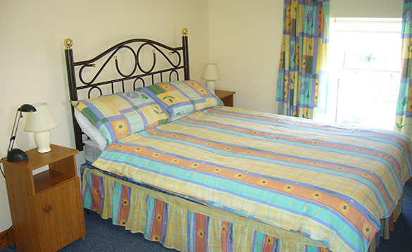 bedroom with double bed with wroguth iron headboard and muticoloured patterned bed spread with matching curtains/