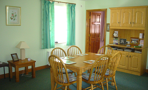 light green painted dining room with pine table and chairs seating six people and pine dresser /