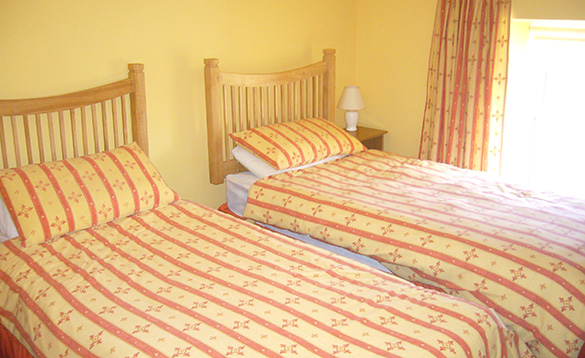sunny yellow painted bedroom with two single beds with yellow and orange striped bed linen/