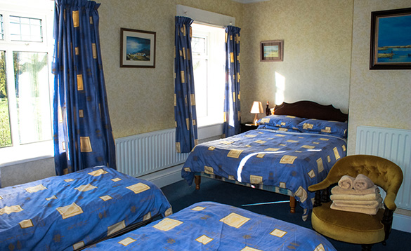 bed room with double and two single beds with blue bed linen with yellow checks and matching curtains to the windows/