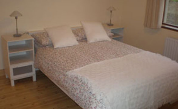 cream painted bedroom with double bed and two cream bedside units/