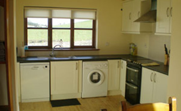 kitchen with cream units and wooden floor and view of hills through the window/