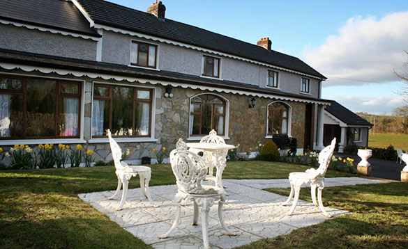 patio with white wrought iron table and chairs infront of stone house with daffodils in flower borders/