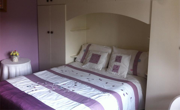 bedroom with double bed with lilac and white striped bed linen/