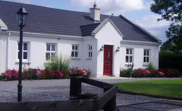 white single storey building with red door at entrance porch and flower beds to the front /