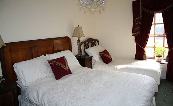 bedroom with double and single beds with white linen and red velvet cushions and curtains/