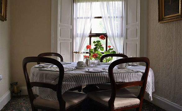 round dining table with four chairs, lace table cloth and places set for breakfast in front of a large window/