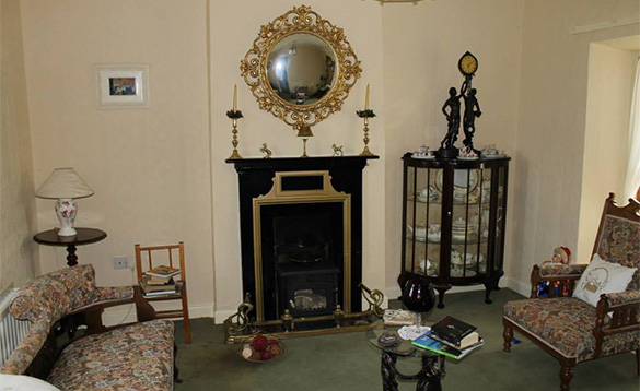 lounge with feature black and gold fireplace with round gold edged mirror above it/