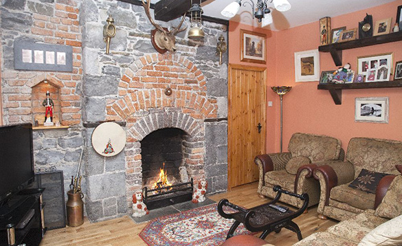 living room with stone and brick feature wall with an open fire burning in the fireplace and a stags head above it/