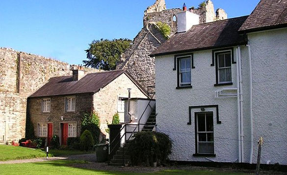 semi detached stone cottage beside the ruins of an abbey/