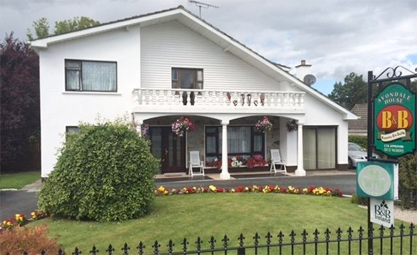 view over a wrought iron fence across a lawn to a two storey house painted white with a veranda to the front with balcony above it/