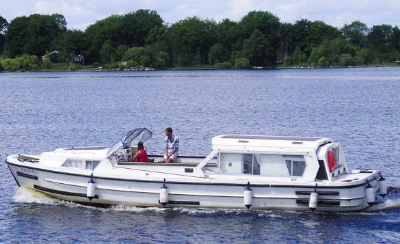 Couple on board a cruiser travelling across Lough Ree in Ireland/