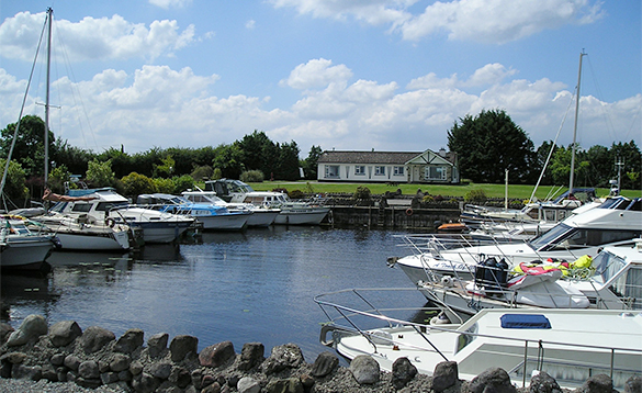 View over a stone wall to cruisers moored in Lough Ree marina, Ireland/