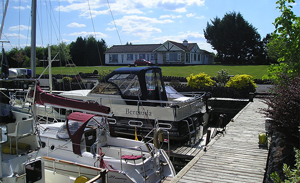 Cruisers in Lough Ree marina moored beside a wooden jetty that leads to a white bungalow/