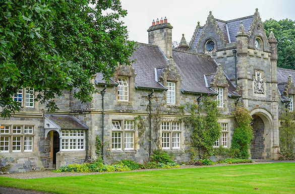 imposing gothic style grey stone building with lawn to the front and climbing plants creeping up the walls/
