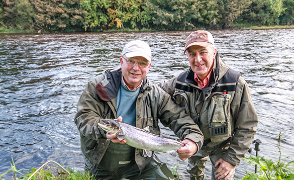 two anglers standing at the edge of a river, one of them holding a grilse fish/
