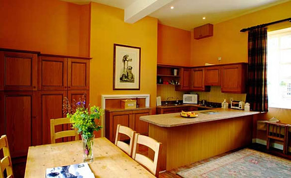 kitchen with dark pine units, breakfast bar and pine table and chairs/
