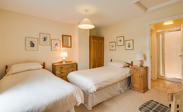 En-suite bedroom with two single beds at the Bridge House, Belle Isle/