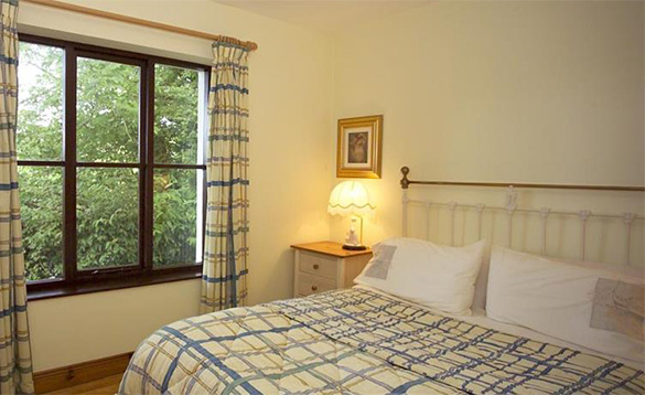 cream painted bedroom with blue and white large checked curtains and double bed with matching linen/