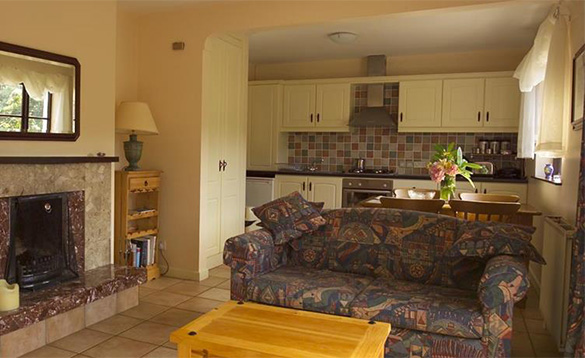 kitchen/living room with tiled floor and cream kitchen units and multi-coloured patterned settee/