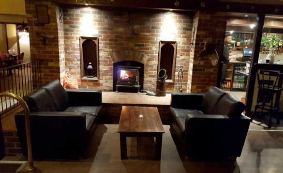 Lounge/bar area of The Hunting Lodge, Newtownstewart with two large leather sofas either side of a pine coffee table in front of a feature brick fireplace with wood burning stove/