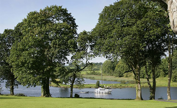 Cruiser boat sailing past the grounds of the Killyhevlin Hotel/